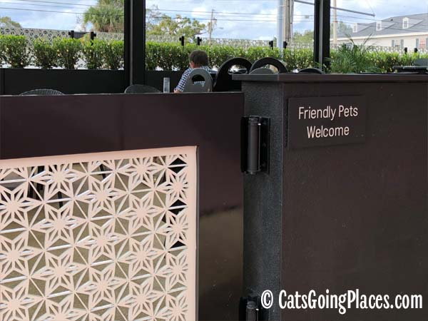 "sign ""Friendly Pets Welcome"" next to gate leading to restaurant patio"