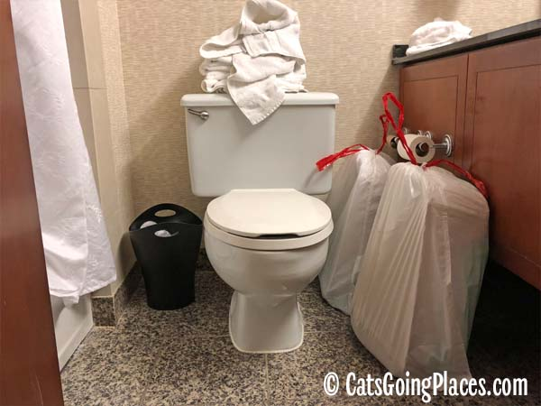 hotel bathroom with litter boxes bagged and ready for housekeeping