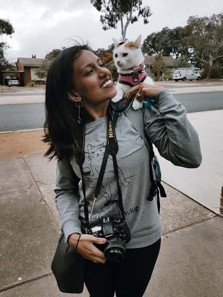 white and calico cat on woman's shoulder. Photo credit catexplorer.com.